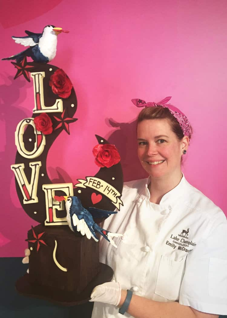 Emily McCracken holding her valentine's day chocolate sculpture in front of a pink wall
