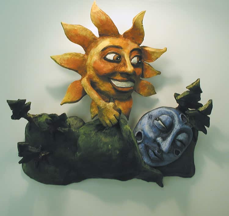 A clay sculpture showing a sun tucking the moon into bed